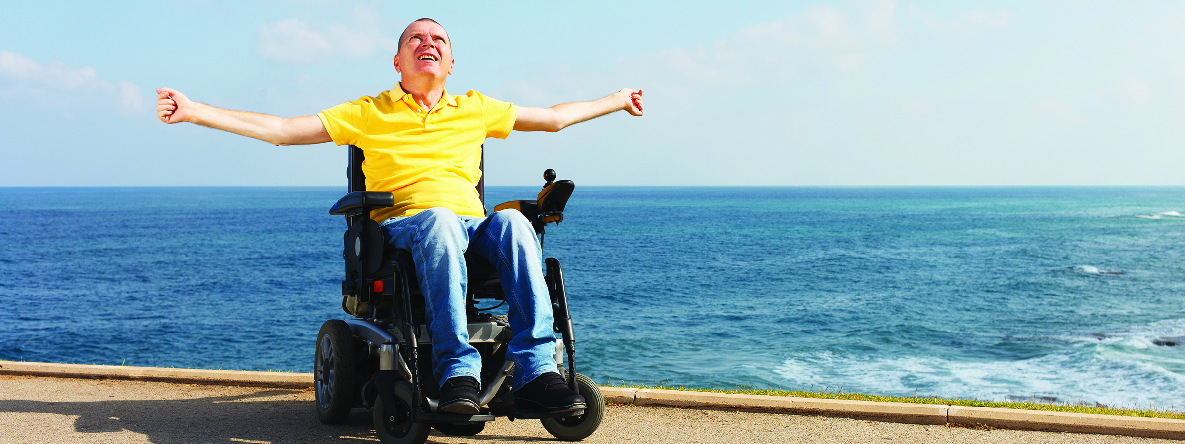 Man in wheelchair by ocean